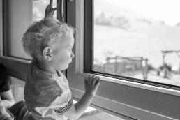 Kind schaut aus dem Fenster bei Fotoshooting Zuhause
