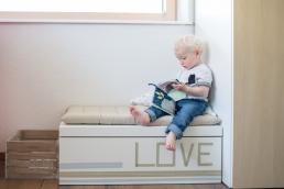 Junge mit Bilderbuch bei Fotoshooting Zuhause