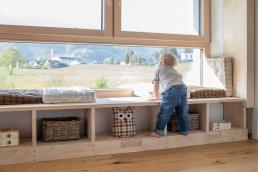 Junge schaut aus Fenster bei Fotoshooting Zuhause