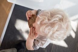 Junge mit Brot bei Fotoshooting Zuhause