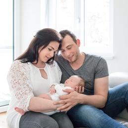 Eltern halten Baby in Armen bei Homestory Fotoshooting