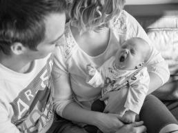 Eltern halten gähnendes Baby im Arm bei Homestory
