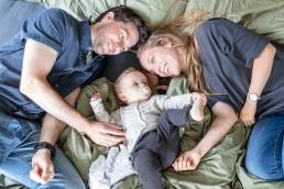 Eltern mit Tochter kuscheln bei Homestory Fotoshooting