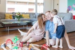 Eltern und Sohn kuscheln Zuhause bei Homestory Fotoshooting