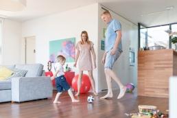 Eltern und Sohn spielen Fußball Zuhause bei Homestory Fotoshooting