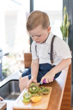 Junge schneidet Kiwi bei Homestory Fotoshooting