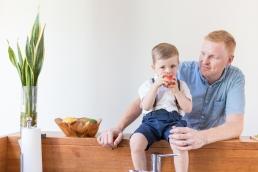 Papa und Sohn beim Äpfel essen Zuhause bei Homestory Fotoshooting