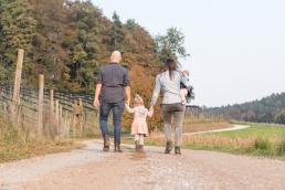 Mädchen Hand in Hand mit den Eltern bei Fotoshooting