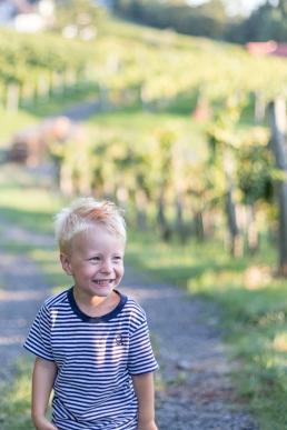 Bub lacht zwischen Weinreben bei Fotoshooting